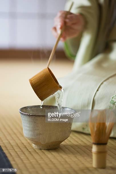 senior woman in kimono performing tea ceremony - ティールーム ストックフォトと画像