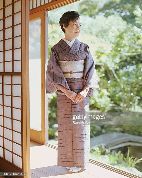 Senior woman in kimono standing in open doorway, looking away