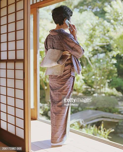 Senior woman in kimono talking on cell phone beside shoji, rear view