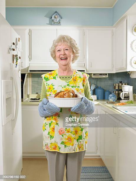 Senior woman in kitchen,  holding dish with roasted chicken
