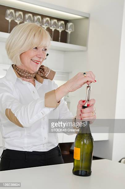 Senior woman in kitchen opening bottle of Prosecco