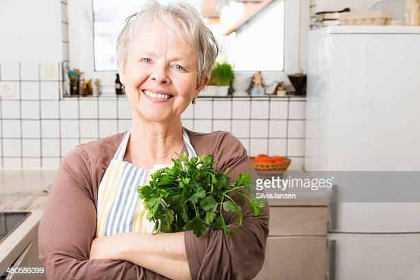 senior Frau in der Küche mit Petersilie Kräutern