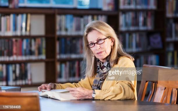 femme aîné dans la bibliothèque faisant la recherche - lunettes de lecture photos et images de collection