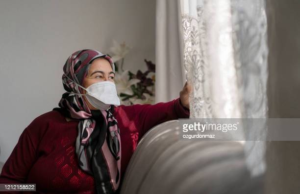 senior woman in medical mask staying at home under quarantine - turkey middle east stock pictures, royalty-free photos & images