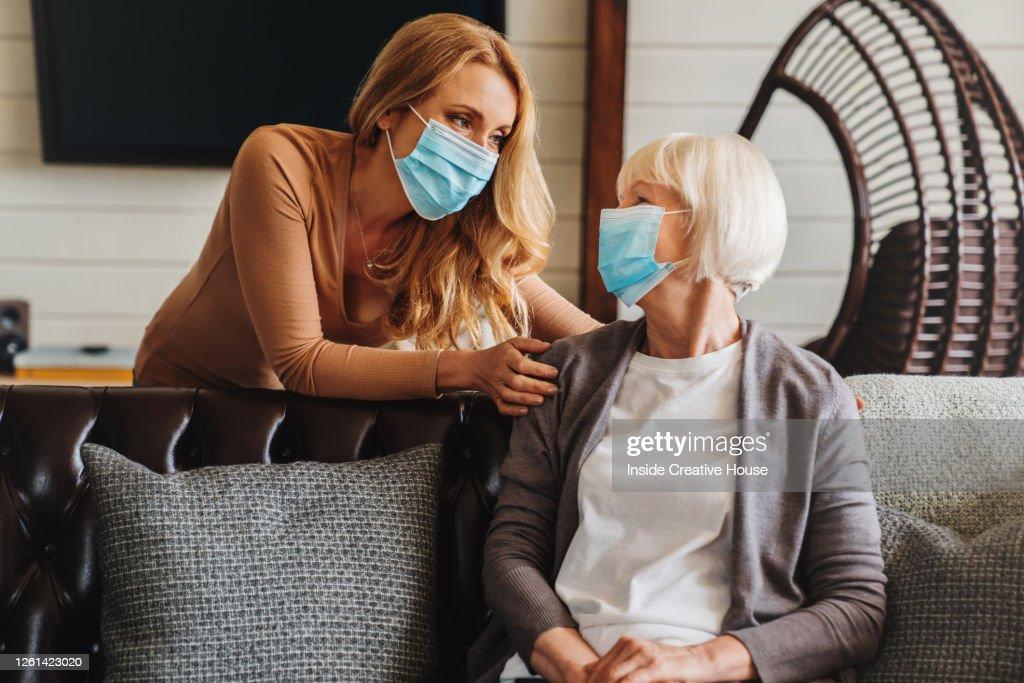 Hogere vrouw in medisch masker met maatschappelijk werker die haar thuis bezoekt : Stockfoto