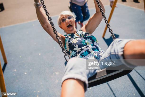 senior woman in mid-air on a swing - young at heart stock pictures, royalty-free photos & images
