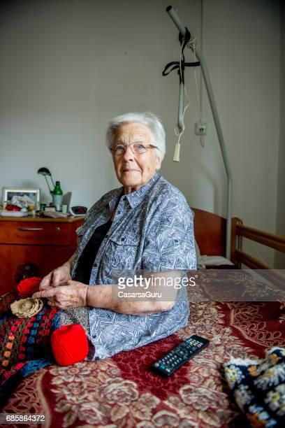 Ältere Frau im Pflegeheim Häkeln für Entspannung