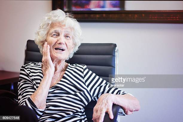 Senior Woman in Office Chair, Smiling