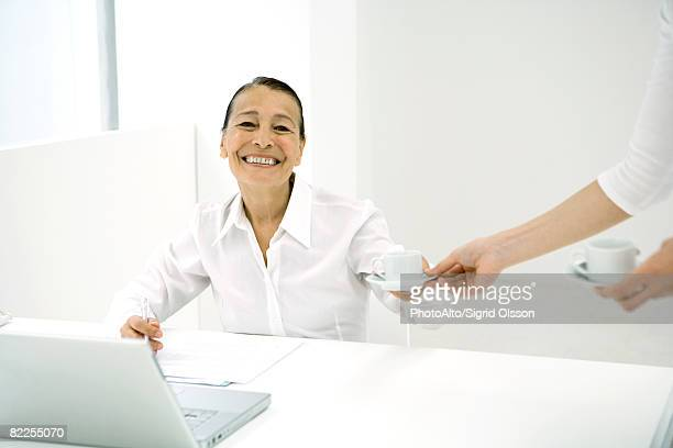 Senior woman in office, taking coffee from colleague, smiling at camera