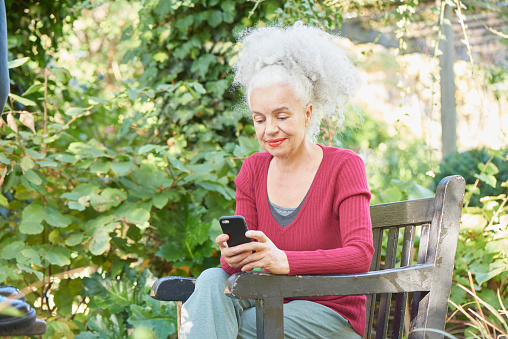senior woman in park with mobile phone - gettyimageskorea