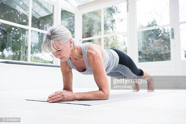 senior woman in plank position in conservatory - active senior woman stock photos and pictures