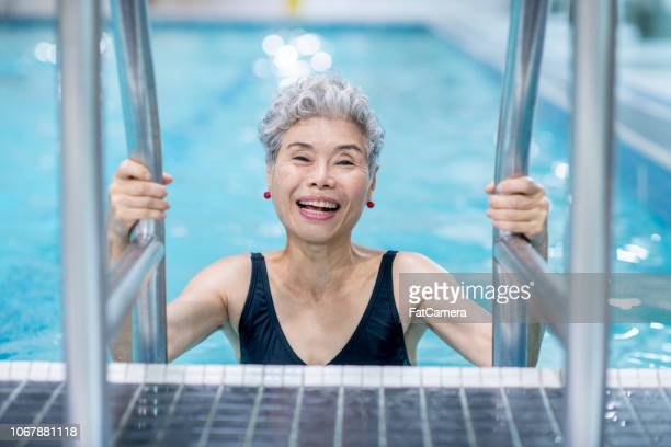 senior woman in pool - swimming stock pictures, royalty-free photos & images