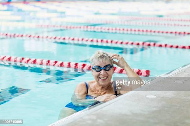 水泳ラップから休憩を取るプールのシニア女性 - スポーツ用語 ラップ ストックフォトと画像