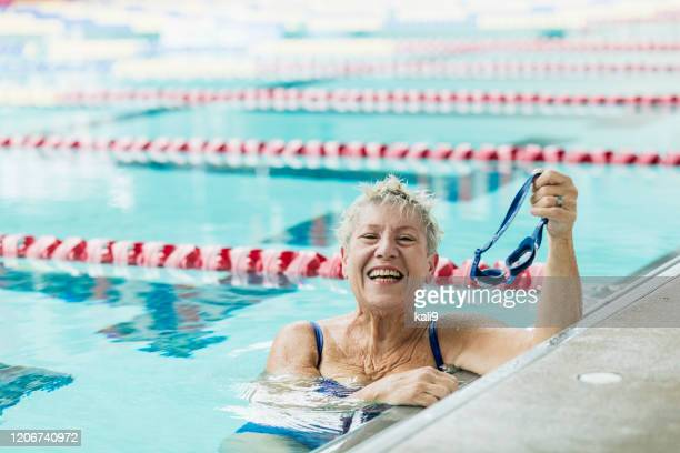 senior woman in pool taking break from swimming laps - length stock pictures, royalty-free photos & images