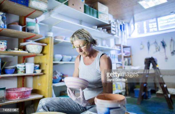 senior woman in pottery workshop, inspecting bowl - sigrid gombert stock-fotos und bilder