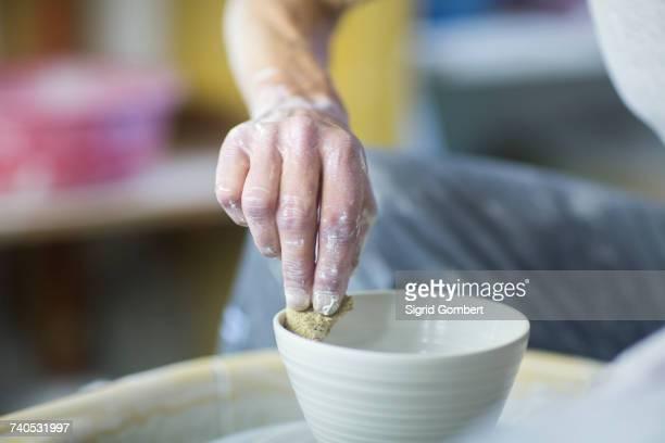 senior woman in pottery workshop, making bowl, close-up - sigrid gombert stock-fotos und bilder