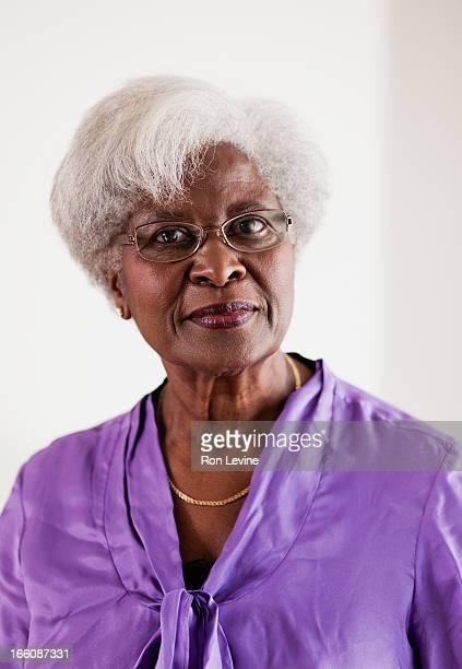 senior woman in purple blouse, portrait - eine seniorin allein stock-fotos und bilder