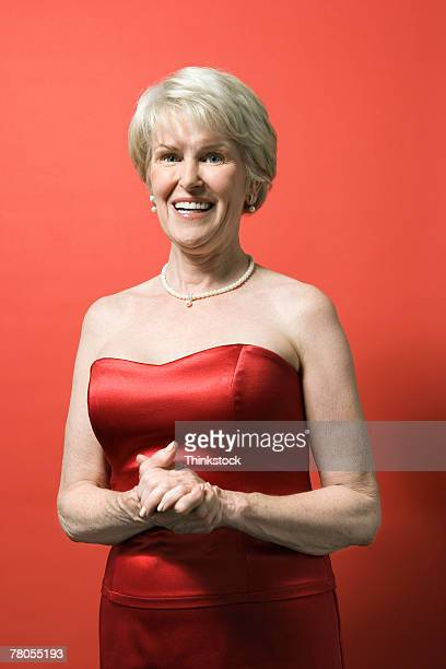 senior woman in red gown - strapless dress stock pictures, royalty-free photos & images