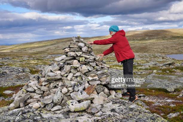 senior woman in red jacket and knitted hat adding one more stone on a cairn. changing weather. - 石塚 ストックフォトと画像