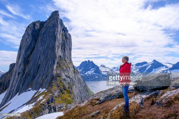 senior woman in red jacket standing looking at the famous mountain segla from the maountain hesten at the island senja northern norway - finn bjurvoll stock pictures, royalty-free photos & images