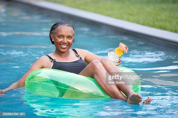 Senior woman in rubber tube relaxing in pool, smiling, portrait