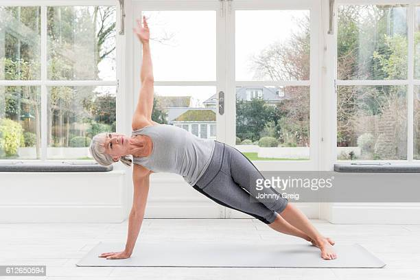 Senior woman in side plank pose with arm raised