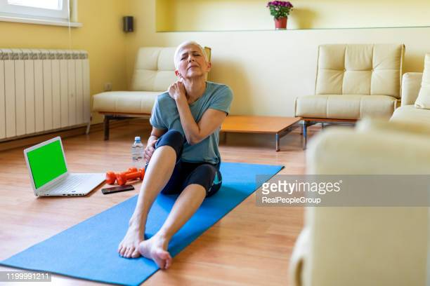 senior woman in sportswear sitting on yoga mat and massaging her shoulder - condition stock pictures, royalty-free photos & images