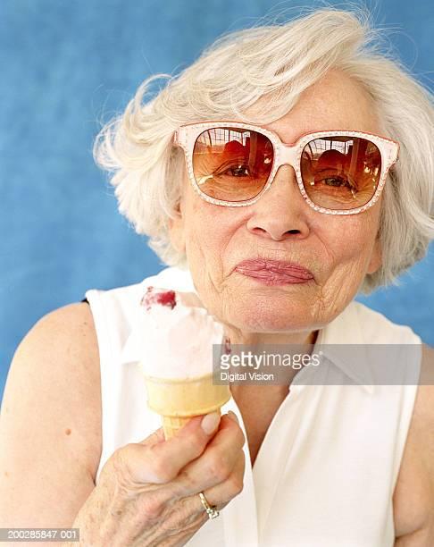 Senior woman in sunglasses holding ice cream cone, smiling, portrait
