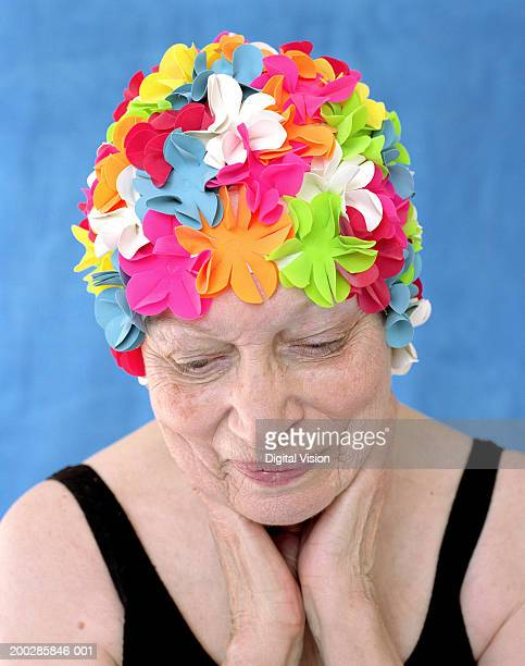 Senior woman in swimming cap and costume, hands on neck, close-up