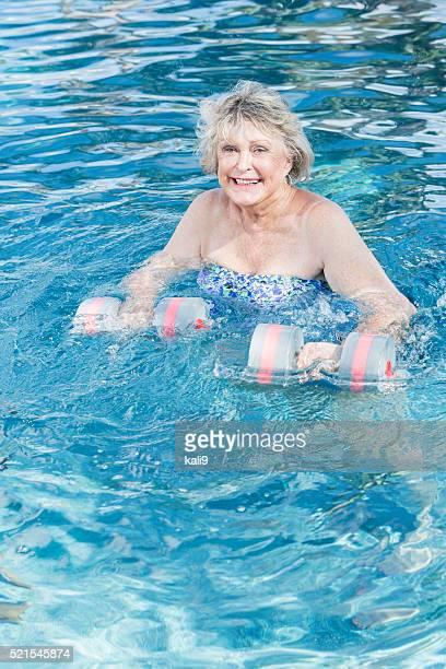 Senior woman in swimming pool doing water aerobics