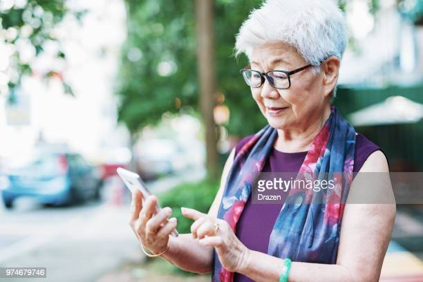 Senior woman in the city using phone to call taxi