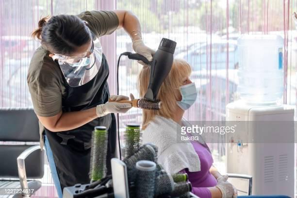 donna anziana nel parrucchiere - hair stylist foto e immagini stock