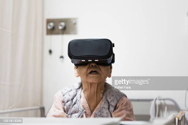 senior woman in the hospital wearing a virtual reality headset - simulatore di realtà virtuale foto e immagini stock