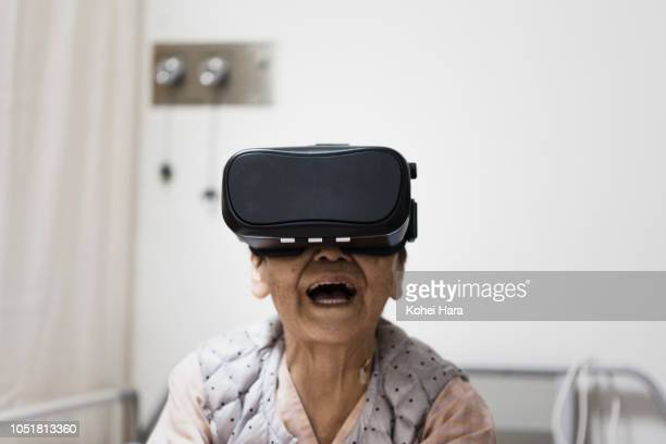 senior woman in the hospital wearing a virtual reality headset - curiosity stock pictures, royalty-free photos & images