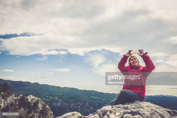 Senior woman in the mountains using her smart phone