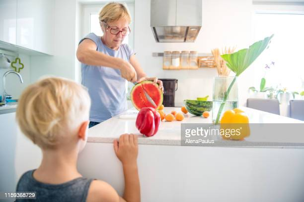 senior woman in the new kitchen cutting watermelon for a blonde little boy - nephew stock pictures, royalty-free photos & images