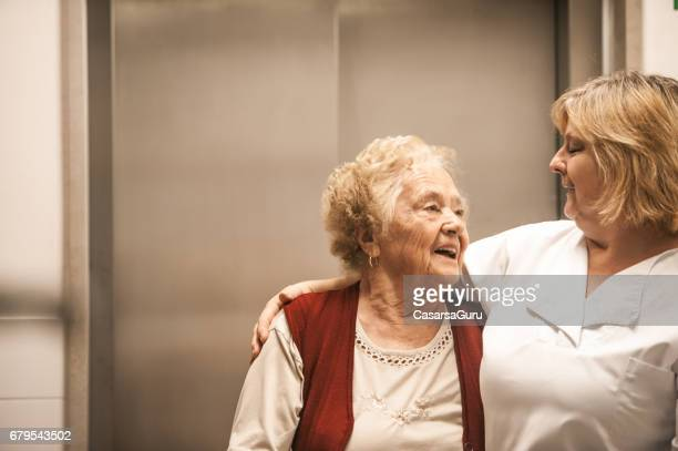 senior woman in the nursing home carrying fresh laundry on mobility walker - residential care stock photos and pictures