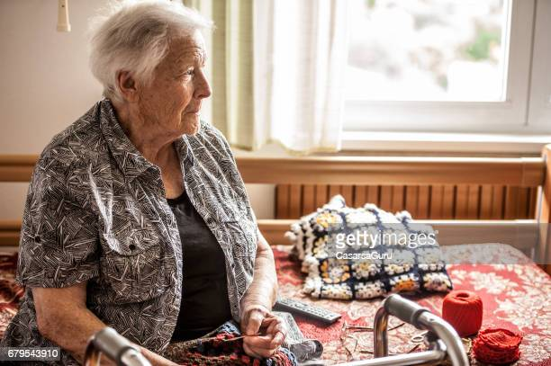 senior woman in the retirement community crocheting - residential care stock photos and pictures