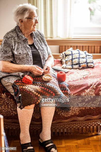 senior woman in the retirement community crocheting - one senior woman only stock pictures, royalty-free photos & images
