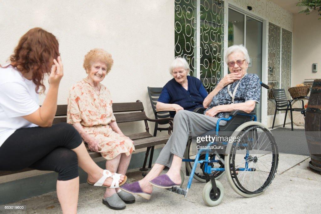 Senior vrouw In het bejaardentehuis socialiseren buiten : Stockfoto