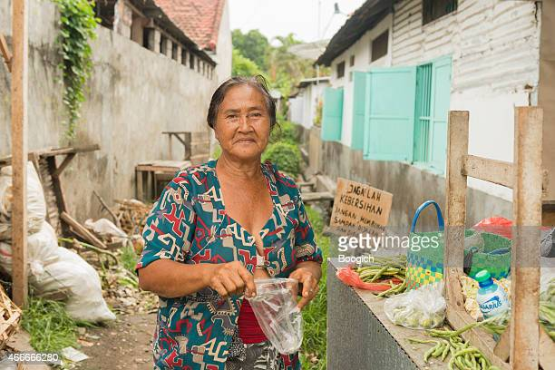 Senior Woman in Traditional Bali Street Market Sells Produce Outdoors