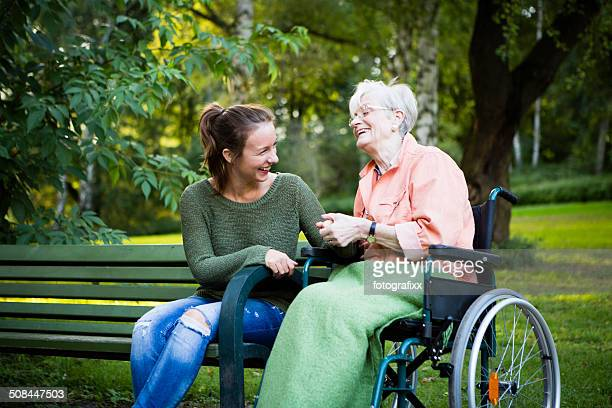 senior woman in wheel chair laughs with young woman