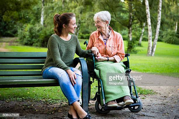senior woman in wheel chair talks with young woman - simple living stock pictures, royalty-free photos & images