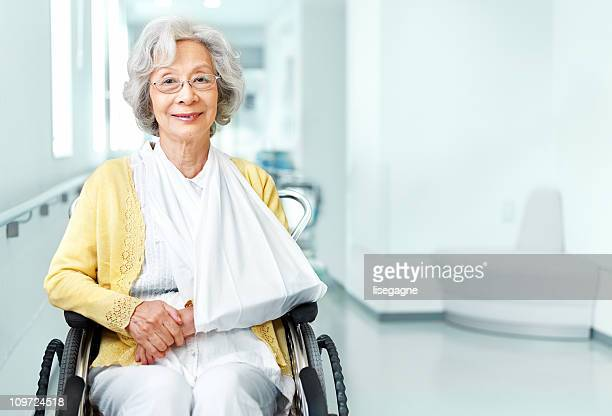 Senior woman in wheelchair and arm sling