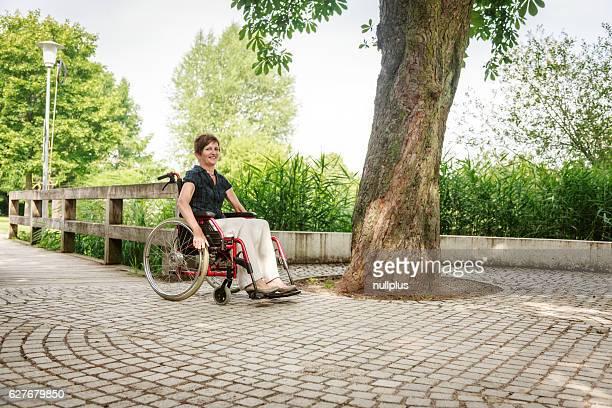 Ältere Frau im Rollstuhl, genießen Sie einen Tag im park