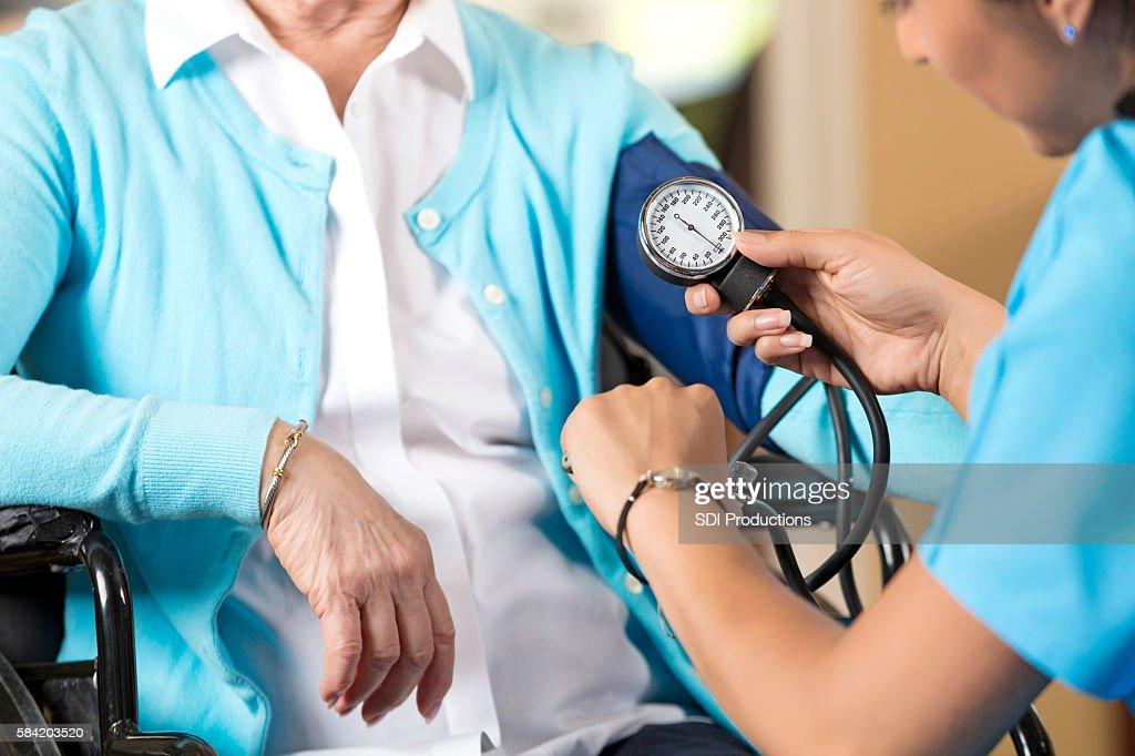 Senior woman in wheelchair getting her blood pressure taken : Stock Photo