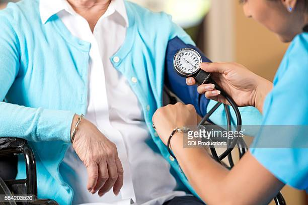 senior woman in wheelchair getting her blood pressure taken - infermiera foto e immagini stock