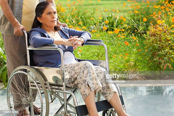 senior woman in wheelchair outdoors - fragility stock pictures, royalty-free photos & images