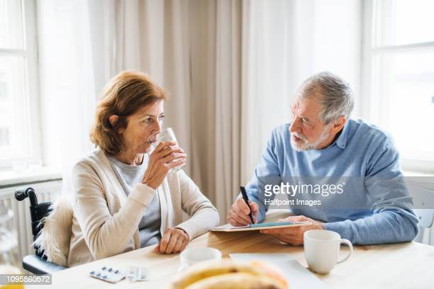 a senior woman in wheelchair sitting at the table at home, taking painkillers and looking at her husband. - taking a pill stock pictures, royalty-free photos & images