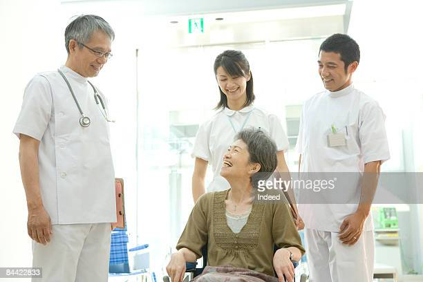 Senior woman in wheelchair smiling to doctor